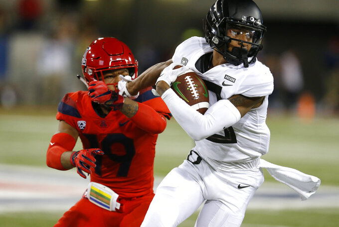 Oregon wide receiver Dillon Mitchell stiff arms Arizona safety Scottie Young Jr. (19) in the first half during an NCAA college football game, Saturday, Oct. 27, 2018, in Tucson, Ariz. (AP Photo/Rick Scuteri)