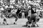 FILE - In this Nov. 8, 1970, file photo, New Orleans Saints' Tom Dempsey (19) moves up to kick a 63-yard field goal as teammate Joe Scarpati holds the ball and Detroit Lions' Alex Karras (71) rushes in while Saints' Bill Cody (66) blocks, in New Orleans. Dempsey, who played in the NFL despite being born without toes on his kicking foot and made a record 63-yard field goal, died late Saturday, April 4, 2020, in New Orleans while struggling with complications from the new coronavirus, his daughter said. He was 73 years old. (AP Photo/File)