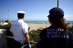 Italian police carry out anti-gathering checks along Ostia beach, near Rome, Sunday, May 24, 2020. Europeans and Americans soaked up the sun where they could, taking advantage of the first holiday weekend since coronavirus restrictions were eased, while European governments grappled with how and when to safely let in foreign travelers to salvage the vital summer tourist season. Italy, which plans to open regional and international borders on June 3 in a bid to boost tourism, is only now allowing locals back to beaches in their own regions — with restrictions. (AP Photo/Andrew Medichini)