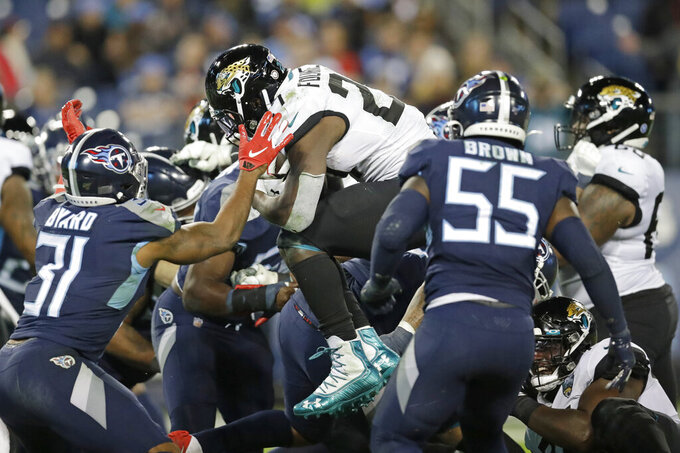 Jacksonville Jaguars running back Leonard Fournette (27) leaps over the goal line as he scores a touchdown on a 1-yard run against the Tennessee Titans in the second half of an NFL football game Sunday, Nov. 24, 2019, in Nashville, Tenn.(AP Photo/James Kenney)