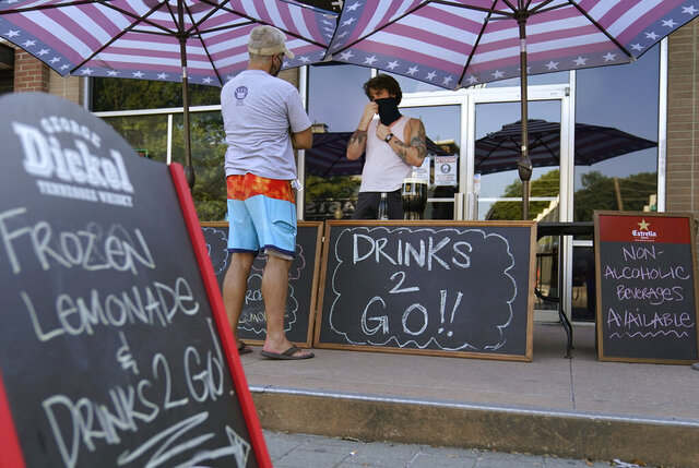 A drinks-to-go table is set up outside the Old Crow bar on Greenville Avenue in Dallas, Thursday, Aug. 13, 2020. Some states and cities in the U.S. are allowing cocktails to-go due to the pandemic. (AP Photo/LM Otero)
