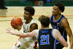 Miami guard Kameron McGusty (23) looks to pass a rebound as Duke forwards Matthew Hurt (21) and Wendell Moore Jr. (0) defend during the first half of an NCAA college basketball game, Monday, Feb. 1, 2021, in Coral Gables, Fla. (AP Photo/Marta Lavandier)