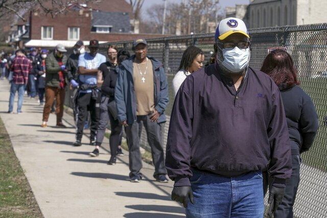 Voters observe social distancing guidelines as they wait in line to cast ballots at Washington High School while ignoring a stay-at-home order over the coronavirus threat to vote in the state's presidential primary election, Tuesday, April 7, 2020, in Milwaukee. (AP Photo/Morry Gash)