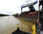 In this Monday, July 22, 2019 photo, a worker watches a crane unload scrap metal along the Tennessee-Tombigbee Waterway in Columbus, Miss. While the waterway hasn't lived up to expectations in terms of traffic or economic development in parts of Alabama and Mississippi, cities including Columbus rely on it for jobs and transportation. (AP Photo/Jay Reeves)