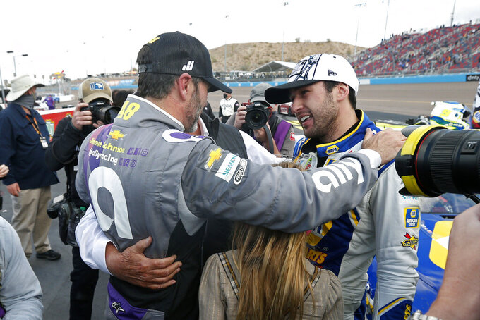 Jimmie Johnson, left, congratulates Chase Elliott following Elliott's season championship victory in the NASCAR Cup Series auto race at Phoenix Raceway, Sunday, Nov. 8, 2020, in Avondale, Ariz. (AP Photo/Ralph Freso)