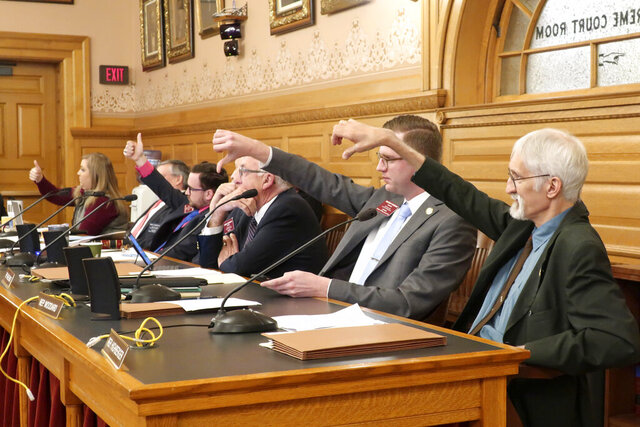 Members of a Kansas House committee indicate whether they want to be recorded as voting yes or no on a proposed amendment to the state constitution on abortion with thumbs-up and thumbs-down signs, Wednesday, Jan. 22, 2020, at the Statehouse in Topeka, Kan. The measure cleared committee on a 15-6 show of hands and would reverse a Kansas Supreme Court decision declaring access to abortion a