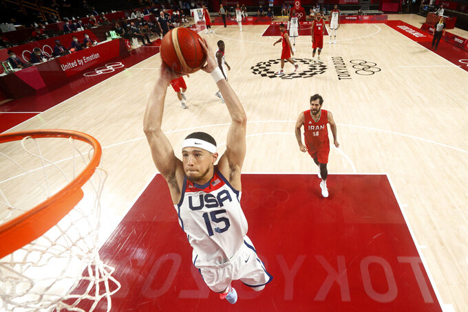 United States' Devin Booker (15) dunks the ball ahead of Iran's Mohammadsamad Nik Khahbahrami (14) during a men's basketball preliminary round game at the 2020 Summer Olympics, Wednesday, July 28, 2021, in Saitama, Japan. (Gregory Shamus/Pool Photo via AP)