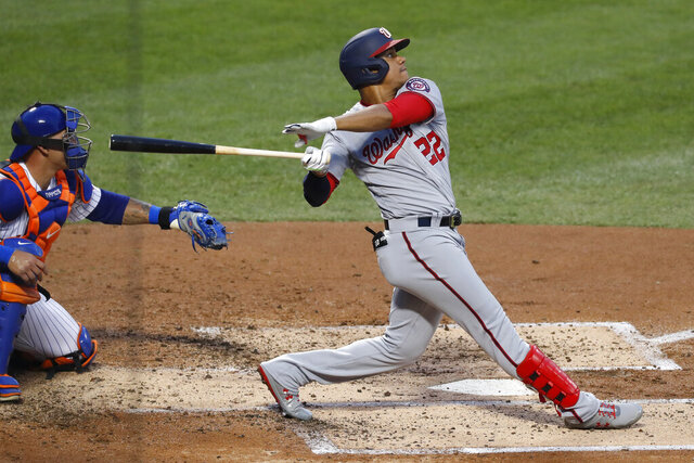 Washington Nationals' Juan Soto, right, watches his two-run home run during the third inning of a baseball game against the New York Mets, Monday, Aug. 10, 2020, in New York. Mets catcher Wilson Ramos, left, looks on. (AP Photo/Kathy Willens)