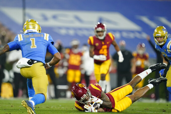 Southern California safety Isaiah Pola-Mao, right, intercepts a pass thrown by UCLA quarterback Dorian Thompson-Robinson, left, during the second quarter of an NCAA college football game Saturday, Dec. 12, 2020, in Pasadena, Calif. (AP Photo/Ashley Landis)