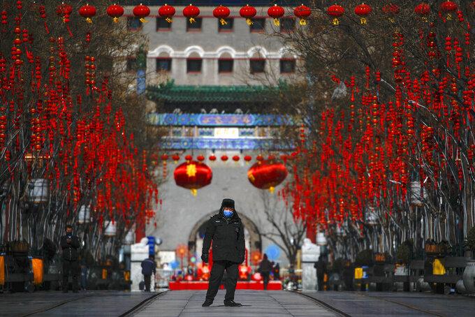 A security guard wearing a face mask walks through a quiet main Qianmen Street, a popular tourist spot, in Beijing, Sunday, Feb. 16, 2020. China reported Sunday a drop in new virus cases for the third straight day, as it became apparent that the country's leadership was aware of the potential gravity of the situation well before the alarm was sounded. (AP Photo/Andy Wong)