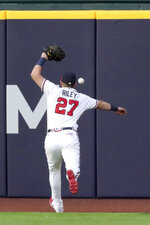 Atlanta Braves left fielder Austin Riley misses a double hit by Los Angeles Dodgers first baseman Max Muncy during the third inning in Game 3 of a baseball National League Championship Series Wednesday, Oct. 14, 2020, in Arlington, Texas.  (Curtis Compton/Atlanta Journal-Constitution via AP)