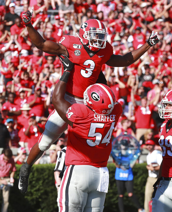Georgia tailback Zamir White (3) is lifted by offensive lineman Justin Shaffer after his touchdown run against Murray State during the second quarter of an NCAA college football game Saturday, Sept. 7, 2019, in Athens, Ga. (Curtis Compton/Atlanta Journal-Constitution via AP)