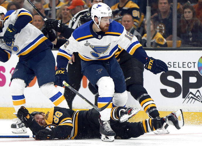 St. Louis Blues' Zach Sanford (12) checks Boston Bruins' David Pastrnak (88), of the Czech Republic, to the ice during the first period in Game 5 of the NHL hockey Stanley Cup Final, Thursday, June 6, 2019, in Boston. (AP Photo/Michael Dwyer)