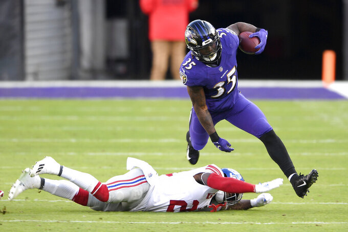 Baltimore Ravens running back Gus Edwards (35) avoids a tackle by New York Giants strong safety Jabrill Peppers (21) during the first half of an NFL football game, Sunday, Dec. 27, 2020, in Baltimore. (AP Photo/Nick Wass)