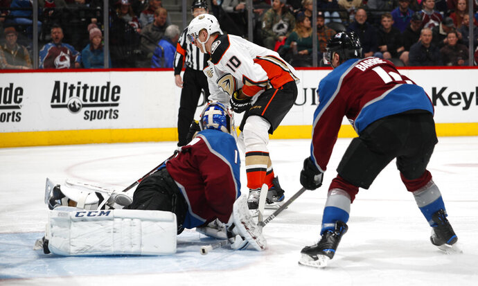 Anaheim Ducks right wing Corey Perry, back, shoots the puck for a goal past Colorado Avalanche goaltender Semyon Varlamov, front left, and defenseman Tyson Barrie during the second period of an NHL hockey game Friday, March 15, 2019, in Denver. (AP Photo/David Zalubowski)