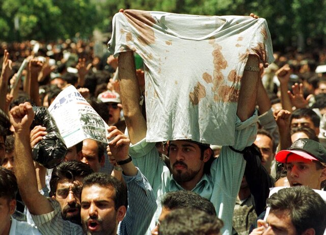 FILE - In this July 12, 1999 file photo, an unidentified student at a rally in Tehran, Iran, holds up the bloody t-shirt of a friend who was injured sometime in the last few days during clashes between police and student demonstrators. The demonstrations that erupted after Iran admitted to accidentally shooting down a Ukrainian jetliner early Wednesday, Jan. 8, 2020, during a tense standoff with the United States, are the latest of several waves of protest going back to the 1979 Islamic Revolution — all of which have been violently suppressed. (AP Photo/Kamran Jebreili, File)