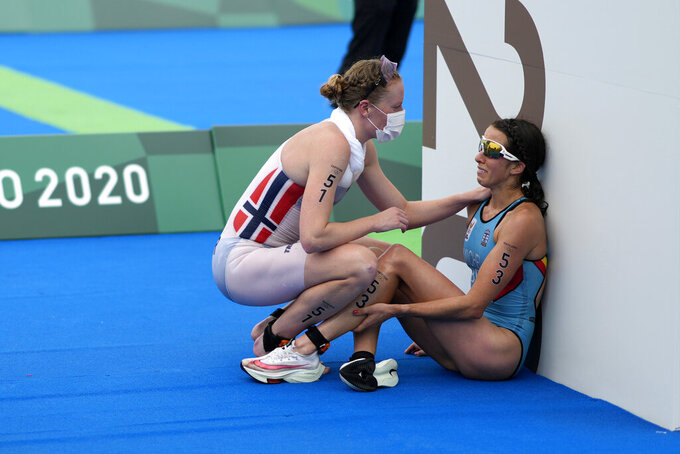 Claire Michel, of Belgium, is assisted by Lotte Miller of Norway after the finish of the women's individual triathlon competition at the 2020 Summer Olympics, in Tokyo, Japan, July 27, 2021. (AP Photo/David Goldman)