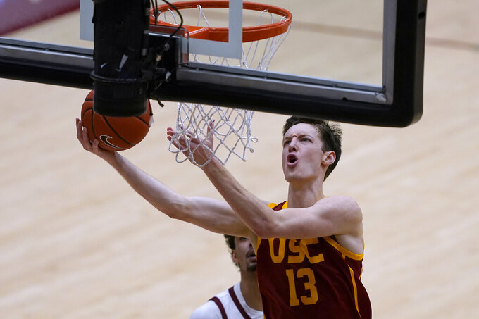 Southern California guard Drew Peterson (13) drives to the basket against Stanford forward Jaiden Delaire, left, during the second half of an NCAA college basketball game in Stanford, Calif., Tuesday, Feb. 2, 2021. Southern California won 72-66.(AP Photo/Tony Avelar)