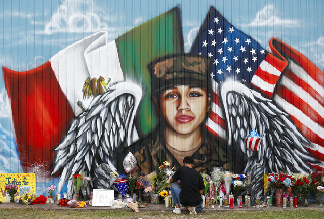 Juan Cruz, boyfriend of Army soldier Vanessa Guillén, kneels in front of a mural honoring her Sunday, July 5, 2020, in Houston. Army investigators have identified the body of a soldier who vanished more than two months ago from a base in Texas, according to a lawyer for the soldier's family. Remains found last week buried near Fort Hood belong to Guillén and Army officials informed her family in Houston Sunday, attorney Natalie Khawam told The Associated Press. (Godofredo A. Vásquez/Houston Chronicle via AP)