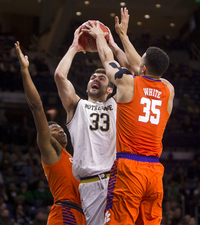 Notre Dame's John Mooney (33) goes up for a shot between Clemson's Clyde Trapp and Javan White (35) during the second half of an NCAA college basketball game Wednesday, March 6, 2019, in South Bend, Ind. Clemson won 64-62. (AP Photo/Robert Franklin)