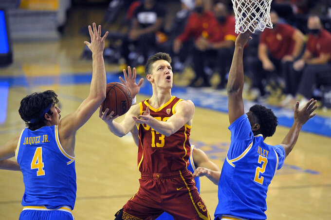 Southern California guard Drew Peterson, center, shoots as UCLA guard Jaime Jaquez Jr., left, and forward Cody Riley defend during the first half of an NCAA college basketball game Saturday, March 6, 2021, in Los Angeles. (AP Photo/Mark J. Terrill)