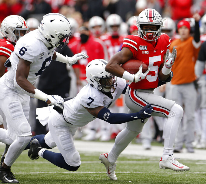 Ohio State receiver Garrett Wilson, right, runs after a catch as Penn State defenders Cam Brown, left, and Jaquan Brisker make the tackle during the first half of an NCAA college football game Saturday, Nov. 23, 2019, in Columbus, Ohio. (AP Photo/Jay LaPrete)