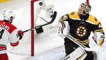 Boston Bruins goaltender Tuukka Rask (40), of Finland, for the puck after a save as Carolina Hurricanes' Justin Williams, left, tries to knock in the rebound during the first period in Game 1 of the NHL hockey Stanley Cup Eastern Conference finals, Thursday, May 9, 2019, in Boston. (AP Photo/Charles Krupa)