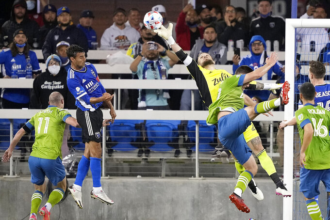 Seattle Sounders goalkeeper Stefan Frei (24) bats the ball away from San Jose Earthquakes forward Chris Wondolowski, second from left, during the second half of an MLS soccer match Wednesday, May 12, 2021, in San Jose, Calif. The Seattle Sounders won 1-0. (AP Photo/Tony Avelar)