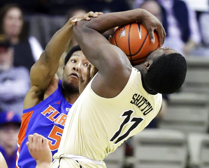 Florida guard KeVaughn Allen (5) fouls Vanderbilt forward Simisola Shittu (11) in the first half of an NCAA college basketball game Wednesday, Feb. 27, 2019, in Nashville, Tenn. (AP Photo/Mark Humphrey)