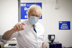 FILE - In this Monday, Jan. 25, 2021 file photo, Britain's Prime Minister Boris Johnson holds a vial of the Oxford AstraZeneca COVID-19 vaccine, during a visit to Barnet FC's ground at the Hive, which is being used as a coronavirus vaccination centre, in London. The European Union's dispute with AstraZeneca has intensified with the Anglo-Swedish drugmaker denying the EU's assertion that it had pulled out of talks on vaccine supplies. AstraZeneca said that it still planned to meet with EU officials in Brussels later in the day. The talks will be the third in as many days. AstraZeneca says the figures in its contract with the EU were targets that couldn't be met because of problems in rapidly expanding production capacity. (Stefan Rousseau/Pool Photo via AP, File)