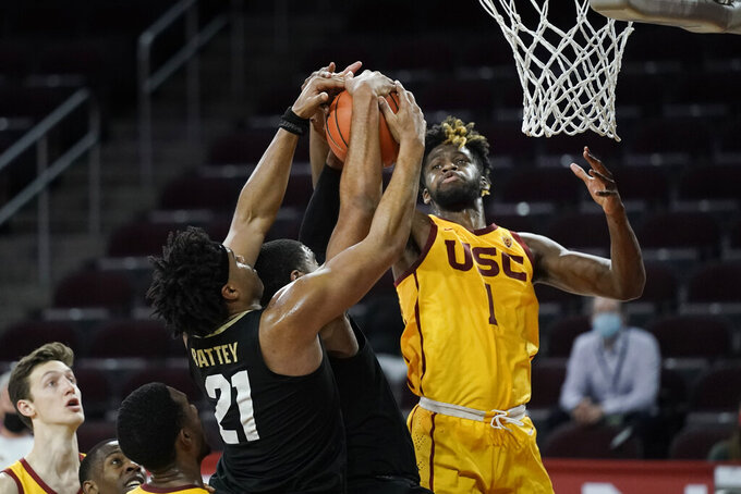 Southern California's Chevez Goodwin, right, fights for a rebound with Colorado's Evan Battey, left, and Jeriah Horne during the second half of an NCAA college basketball game Thursday, Dec. 31, 2020, in Los Angeles. Colorado won 72-62. (AP Photo/Jae C. Hong)