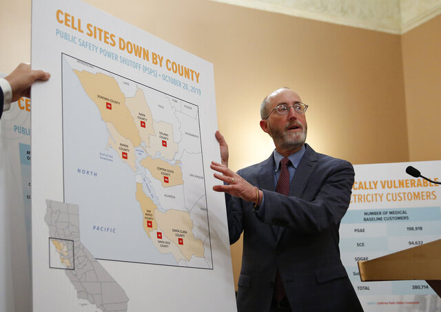 FILE - In this Jan. 8, 2020, file photo, Sen. Steve Glazer, D-Orinda, displays a chart showing cell tower sites that were shut down during power outages in 2019, in Sacramento, Calif. Regulators will require 72 hours of backup power at cell towers in emergency situations, including electricity shutoffs during fire seasons. The California Public Utilities Commission voted unanimously Thursday, July 16, 2020, to adopt the measure. Last fire season, more than a million people lost service during planned blackouts. AT&T said after the vote that it is focused on ensuring that backup power is available routinely during public safety power shut-offs. (AP Photo/Rich Pedroncelli, File)