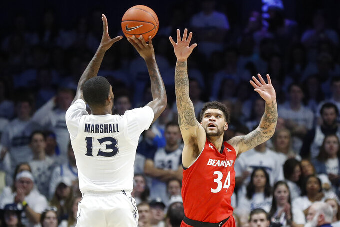 Xavier's Naji Marshall (13) shoots over Cincinnati's Jarron Cumberland (34) during the first half of an NCAA college basketball game, Saturday, Dec. 7, 2019, in Cincinnati. (AP Photo/John Minchillo)