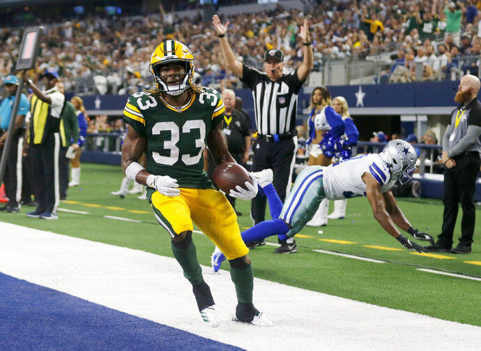 Green Bay Packers' Aaron Jones (33) reaches the end zone for a touchdown in front of Dallas Cowboys' Byron Jones, rear, during the second half of an NFL football game in Arlington, Texas, Sunday, Oct. 6, 2019. (AP Photo/Michael Ainsworth)