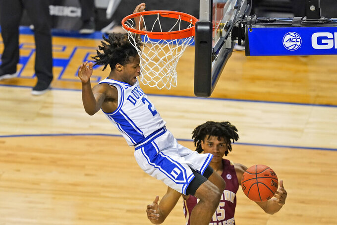 Duke guard DJ Steward (2) dunks over Boston guard Demarr Langford Jr. (15) during the first half of an NCAA college basketball game in the first round of the Atlantic Coast Conference tournament in Greensboro, N.C., Tuesday, March 9, 2021. (AP Photo/Gerry Broome)