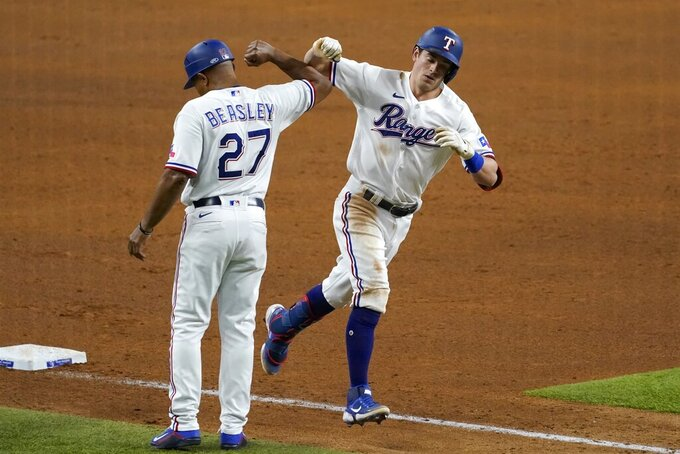 Texas Rangers third base coach Tony Beasley (27) and Nick Solak, right, celebrate as Solak jogs home after hitting a solo home run off New York Yankees starting pitcher Jameson Taillon during the fifth inning of a baseball game in Arlington, Texas, Tuesday, May 18, 2021. (AP Photo/Tony Gutierrez)