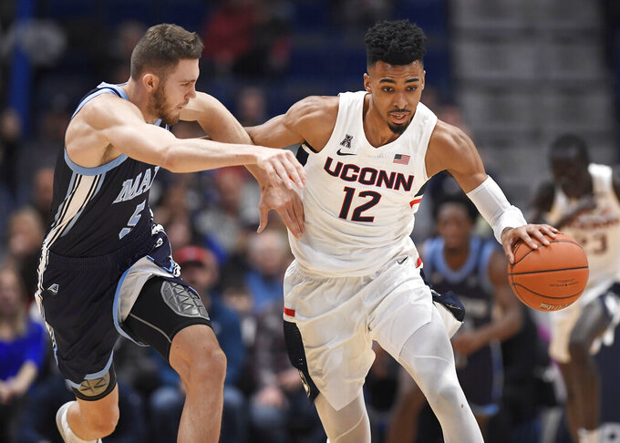 Connecticut's Tyler Polley is pressured by Maine's Nedeljko Prijovic, left, during the first half of an NCAA college basketball game Sunday, Dec. 1, 2019, in Hartford, Conn. (AP Photo/Jessica Hill)