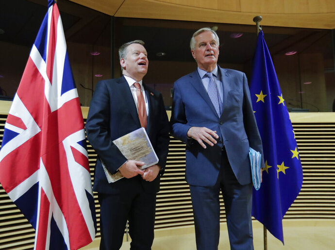 In this Monday, March 2, 2020 file photo, European Commission's Head of Task Force for Relations with the United Kingdom Michel Barnier, right, speaks with the British Prime Minister's Europe adviser David Frost during the start of the first round of post -Brexit trade talks between the EU and the UK, at EU headquarters in Brussels. Slowed by the coronavirus pandemic and whipped up by a British-imposed deadline, talks between the EU and the UK on a future relationship in the wake of Brexit are struggling to make significant progress. A third negotiation session is drawing to a close on Friday, May 15, 2020 but so far, just over 100 days after the official exit of the UK from the EU, fundamental gaps still exist. (Olivier Hoslet, Pool Photo via AP, File)