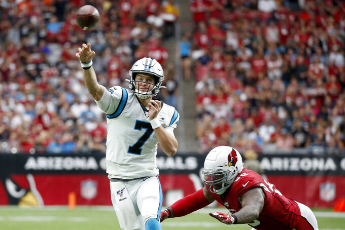 Carolina Panthers quarterback Kyle Allen (7) throws a touchdown pass as Arizona Cardinals center Mason Cole pursues during the first half of an NFL football game, Sunday, Sept. 22, 2019, in Glendale, Ariz. (AP Photo/Ross D. Franklin)