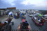 FILE - In this Dec. 24, 2019 file photo, truckloads of civilians flee a Syrian military offensive in Idlib province, on the main road near Hazano, Syria. Hundreds of thousands of Syrians have fled recent government bombardment of the last rebel bastion, the northwestern Idlib province, seeking shelter from harsh winter weather in muddy tents and half-constructed buildings. As government forces advance, areas deemed safe are rapidly shrinking. (AP Photo/Ghaith al-Sayed, File)