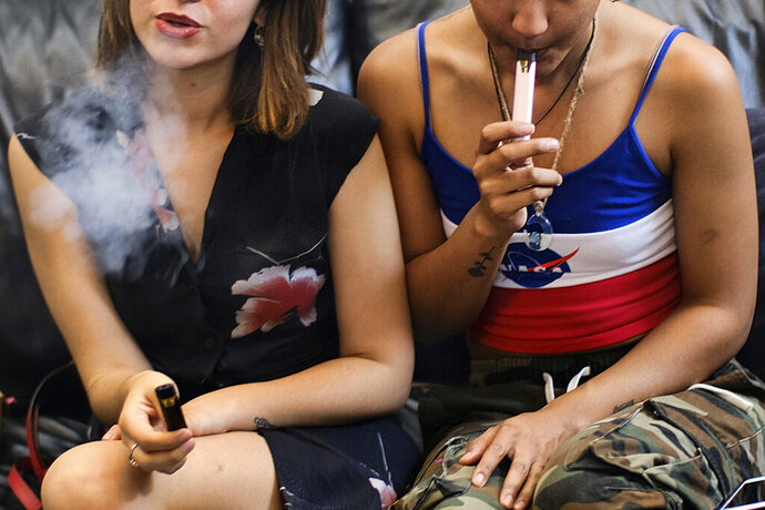 FILE - In this Saturday, June 8, 2019, file photo, two women smoke cannabis vape pens at a party in Los Angeles. Major legal marijuana businesses in California are urging the state to adopt tougher safety rules for ingredients and devices used in vaping. Recommendations from the industry group, Legal Cannabis for Consumer Safety, follow a national outbreak of mysterious and sometimes fatal lung illnesses apparently linked to vaping. Most cases have involved products that contain the marijuana compound THC, typically obtained from illegal sources. The group also wants more funds to close illegal shops. (AP Photo/Richard Vogel, File)