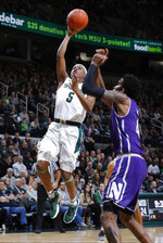 Michigan State's Cassius Winston, left, goes up for a layup against Northwestern's Vic Law during the first half of an NCAA college basketball game, Wednesday, Jan. 2, 2019, in East Lansing, Mich. (AP Photo/Al Goldis)