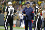 Houston Texans coach Bill O'Brien gets ready to throw the challenge flag as he talks with officials during the second half of the team's NFL preseason football game against the Green Bay Packers on Thursday, Aug. 8, 2019, in Green Bay, Wis. (AP Photo/Jeffrey Phelps)