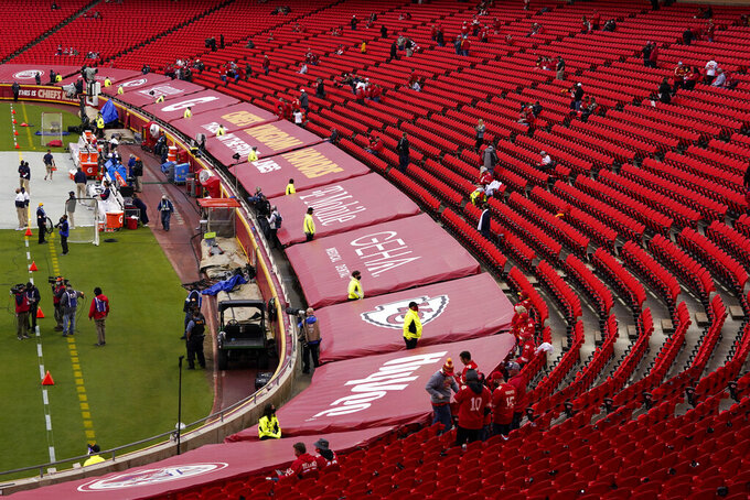 Fans watch as players warm up before an NFL football game between the Kansas City Chiefs and the Houston Texans Thursday, Sept. 10, 2020, in Kansas City, Mo. A reduced number of fans are being allowed in to see the game. (AP Photo/Jeff Roberson)