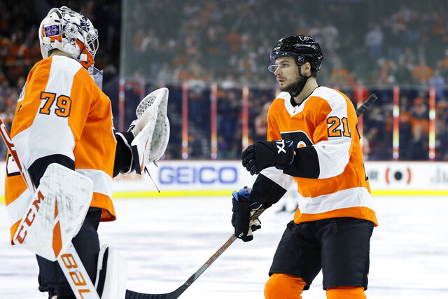 Philadelphia Flyers' Scott Laughton, right, celebrates with Carter Hart after Laughton's goal during the first period of an NHL hockey game against the Winnipeg Jets, Saturday, Feb. 22, 2020, in Philadelphia. (AP Photo/Matt Slocum)