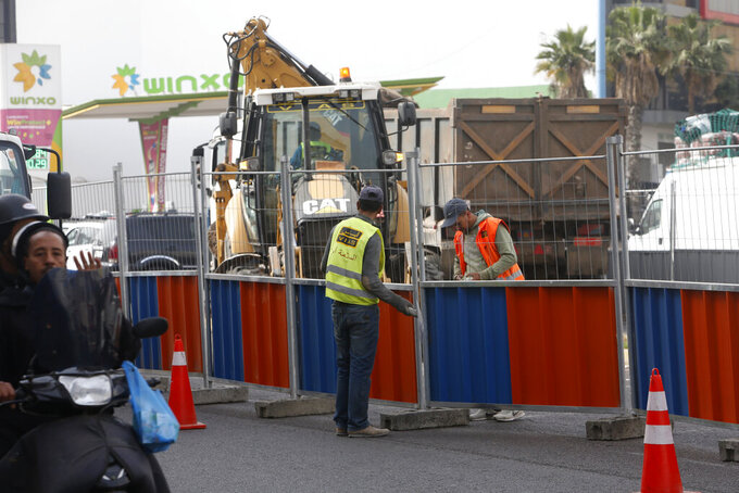 Workmen in Casablanca, Morocco, Tuesday, April 6, 2021. Moroccan authorities have announced the discovery of a new local variant of the coronavirus and extended an overnight curfew as infections rise again. (AP Photo/Abdeljalil Bounhar)