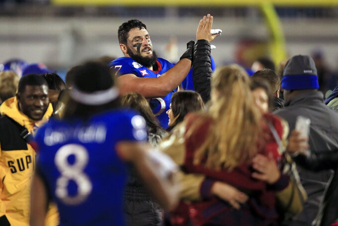 Kansas offensive lineman Kevin Feder (67) high-fives fans following an NCAA college football game against Texas Tech in Lawrence, Kan., Saturday, Oct. 26, 2019. Kansas defeated Texas Tech 37-34. (AP Photo/Orlin Wagner)