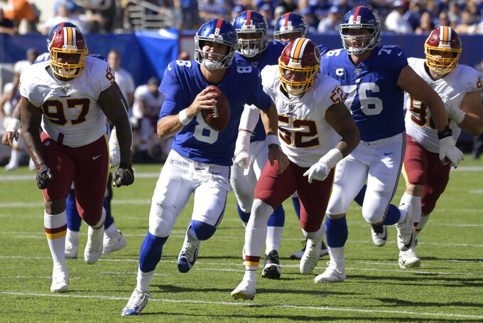 New York Giants quarterback Daniel Jones, second from left, runs the ball during the first half of an NFL football game against the Washington Redskins, Sunday, Sept. 29, 2019, in East Rutherford, N.J. (AP Photo/Bill Kostroun)