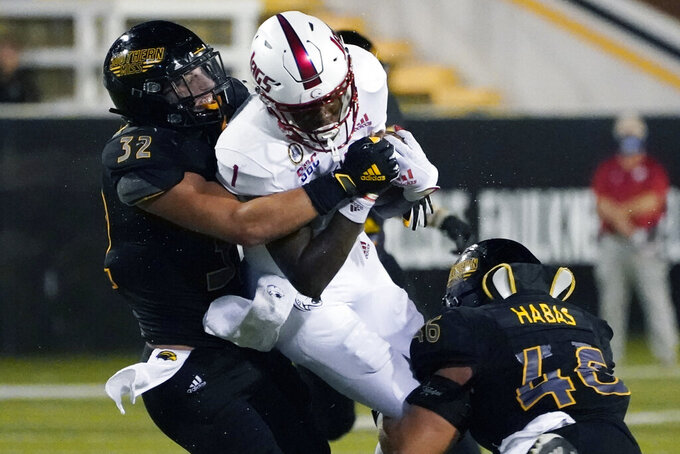 Southern Mississippi linebackers Hayes Maples (32) and Averie Habas (46) tackle South Alabama quarterback Desmond Trotter (1) after a short run during the first half of an NCAA college football game in Hattiesburg, Miss., Thursday, Sept. 3, 2020. (AP Photo/Rogelio V. Solis)
