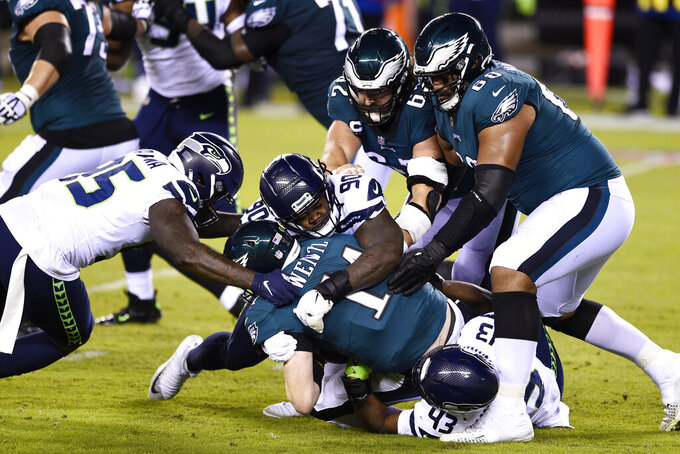 Philadelphia Eagles' Carson Wentz (11) is tackled by Seattle Seahawks' Carlos Dunlap (43), Jarran Reed (90) and Benson Mayowa (95) during the first half of an NFL football game, Monday, Nov. 30, 2020, in Philadelphia. (AP Photo/Derik Hamilton)